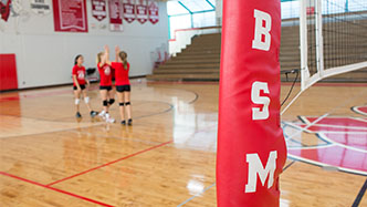 """BSM"" on the side of a volleyball court post with female volleyball students in the background."