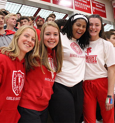 Red Knight students pose for photo as they cheer at a pep fest