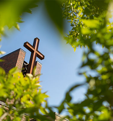 View of the large cross on top of the BSM chapel, peering through a sunny tree.