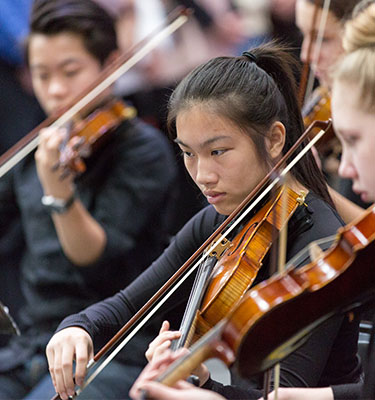 Student playing violin in orchestra