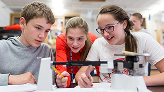 Three students weighing an item in science class on a scale.