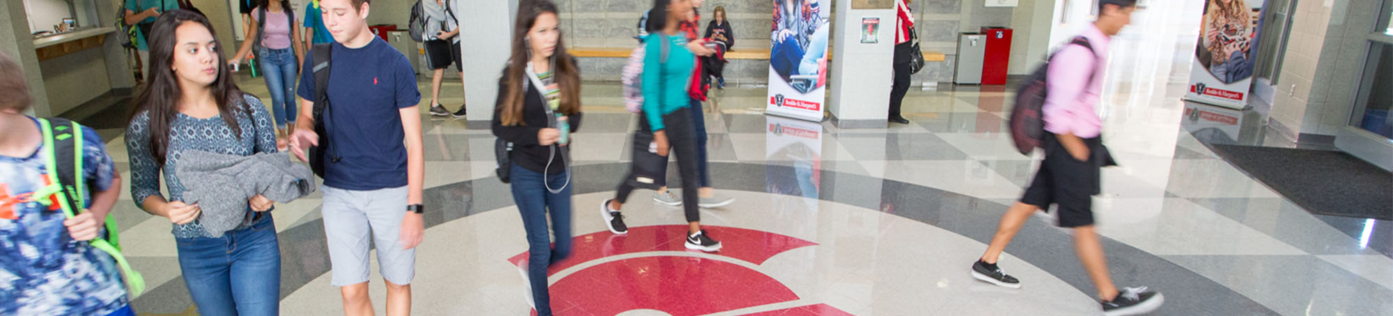 Students walk through front entrance with the knight head on the floor.