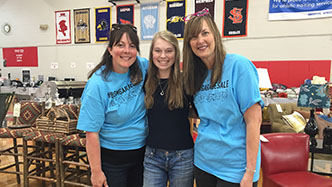 Two Red Knight parents with a students pose as they volunteer at the annual Treasure Hunt Garage Sale.