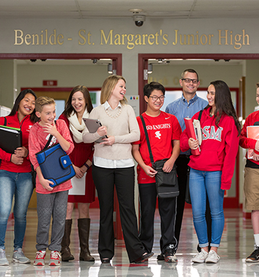 Junior high students, faculty and staff pose for a photo laughing in the junior high hallway