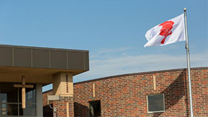Red Knight flag blowing in the wind next to the cross outside of the school.