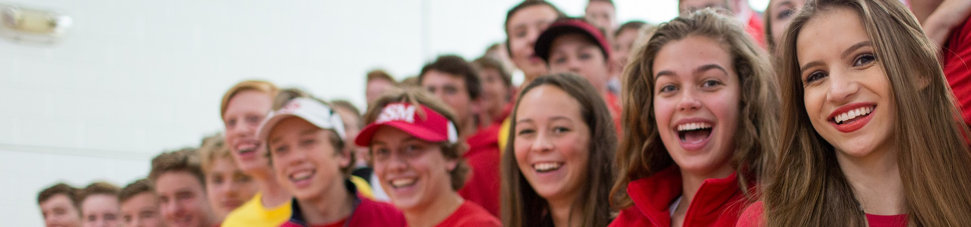 Up close shot of students smiling and laughing at a school pepfest